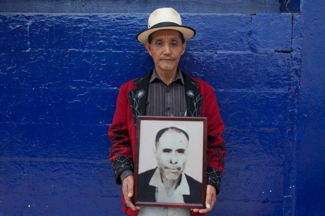 An Ixil Mayann man holds a photo of his father, who was killed in the 1980's by the Guatemalan military.