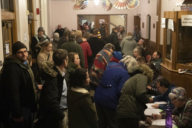People gather to check-in to vote at the caucus in Ames, Iowa.