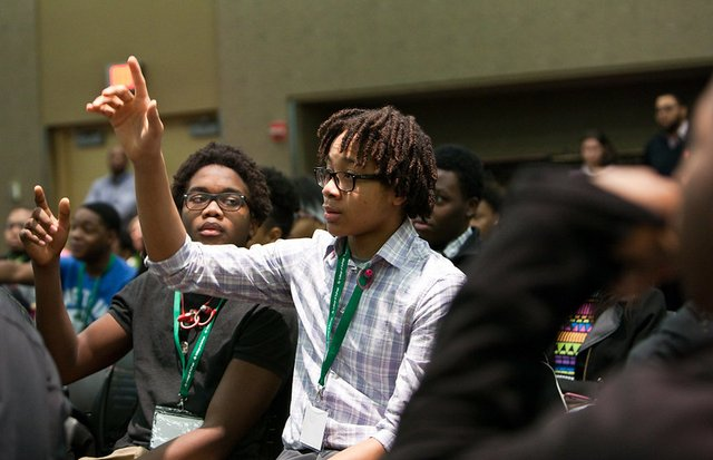 Student at conference raising hand