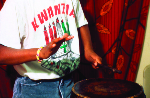 Description-_Young_man_playing_drums_during_Kwanzaa_celebration,_three-quarter_length_portrait._(2536626922).jpg