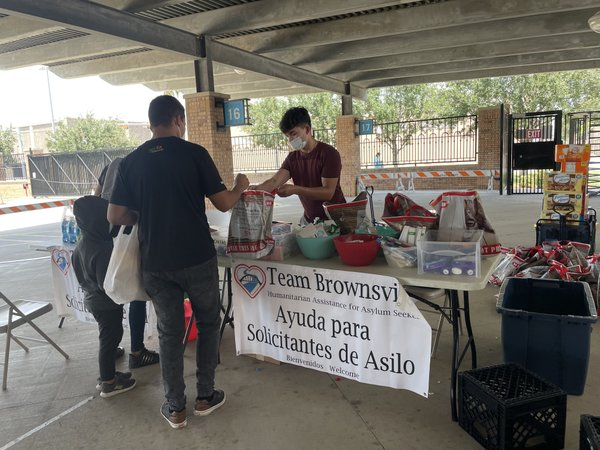 Moises Zuniga of Team Brownsville helps migrant family at supply table outside bus station in Brownsville, Texas on August 7, photo by Wandy Cruz.jpg