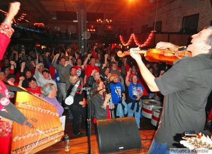 "(Daithi Wolfe fiddles and sings ""Solidarity Forever"" with the crowd at the High Noon Saloon – photo by Rebecca Kemble)"