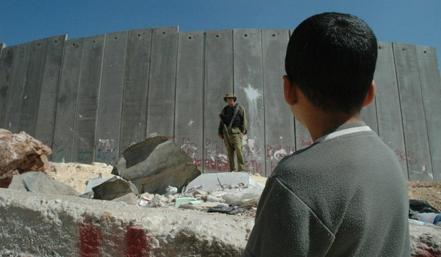 Boy_and_soldier_in_front_of_Israeli_wall.jpg.jpe