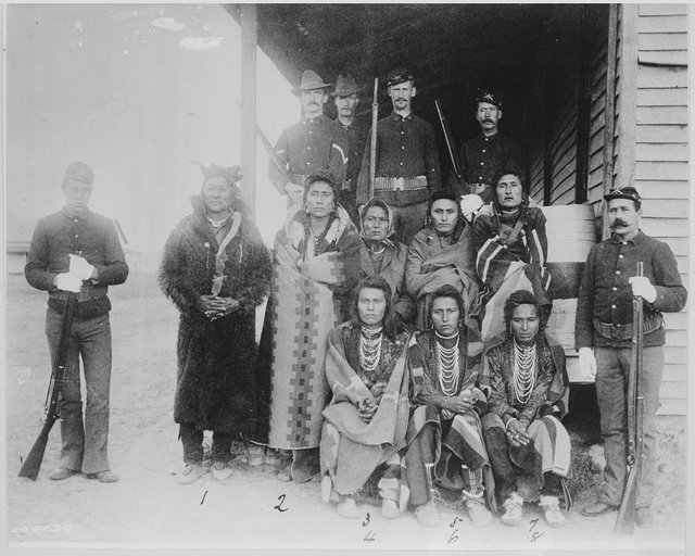 1125px-Eight_Crow_prisoners_under_guard_at_Crow_agency,_Montana,_1887_-_NARA_-_531126.jpg